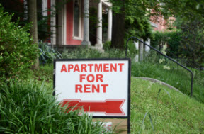 Red and white Apartment For Rent sign in front of property