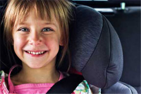 A smiling child in car seat.