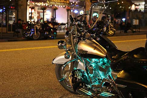 Beautiful motorcycle parked on street with street lights and businesses in background