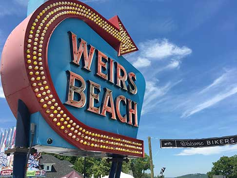 Weirs Beach lighted sign with an arrow pointing to the beach