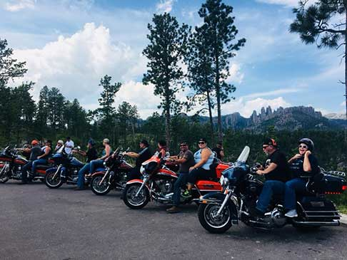 Several motorcyclists and motorcycles parked and ready to ride with the Black Hills in the background