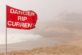 A red rip current warning flag on the beach
