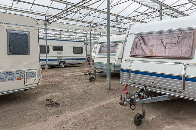 A handful of RVs in a winter storage facility